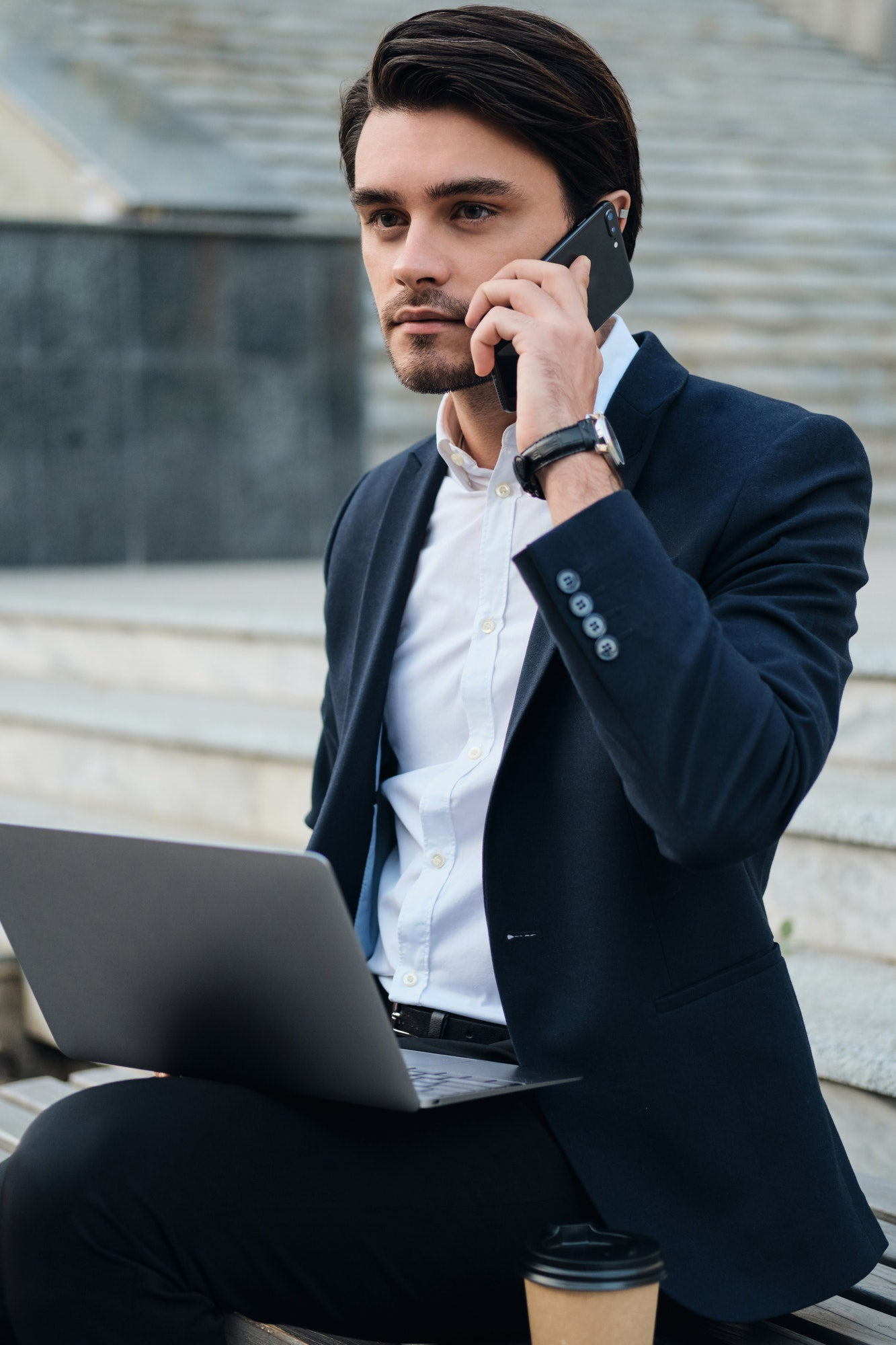 Young businessman in suit sitting on bench with laptop dreamily looking aside talking on cellphone